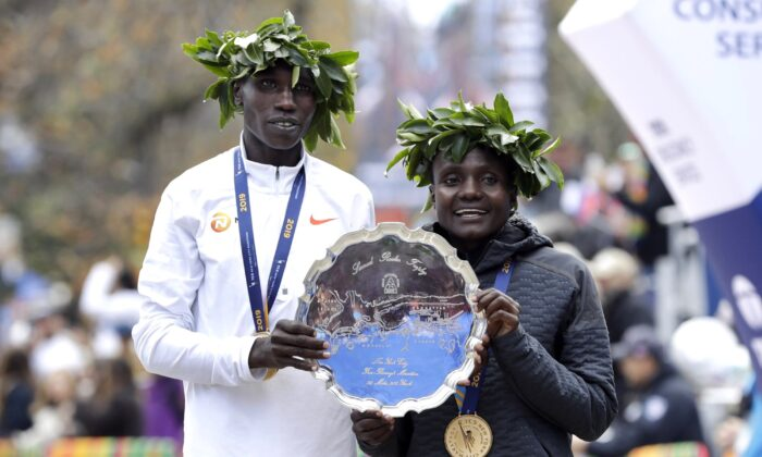 Geoffrey Kamworor (L) and Joyciline Jepkosgei, both of Kenya, pose for photos as the men's and women's winners of the New York City Marathon, in New York's Central Park on Nov. 3, 2019. (Richard Drew/AP Photo)