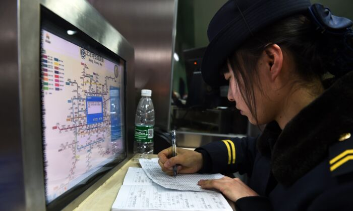 An attendant works in front of a subway map at a subway station in Beijing on Dec. 29, 2014. (GREG BAKER/AFP via Getty Images)