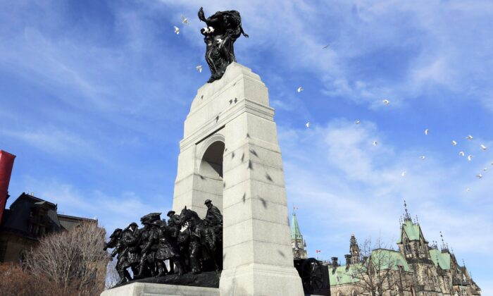 Doves fly over the National War Memorial, also known as The Response, to commemorate the 100th anniversary of the Battle of Vimy Ridge, in Ottawa on April 9, 2017. (THE CANADIAN PRESS/Fred Chartrand)