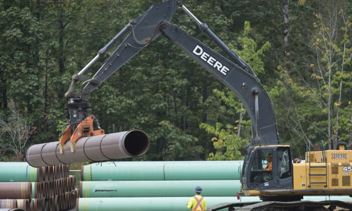 Workers stack pipeline pipes at a Trans Mountain facility near Hope, B.C., on Aug. 22, 2019. (THE CANADIAN PRESS/Jonathan Hayward)