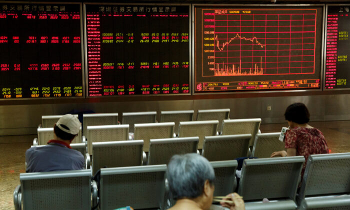 People sit in front of a board showing market information at a securities brokerage house in Beijing, China on Aug. 5, 2019. (Thomas Peter/Reuters)