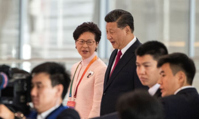 Hong Kong's Chief Executive Carrie Lam and Chinese leader Xi Jinping arrive at the opening ceremony of the Hong Kong-Zhuhai-Macau Bridge at the Zhuhai Port terminal on October 23, 2018. (FRED DUFOUR/AFP via Getty Images)