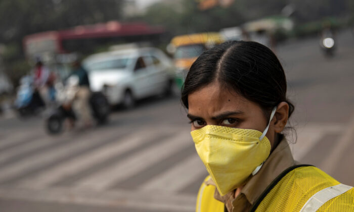 A policewoman wears a mask to protect herself from air pollution at a junction during restrictions on private vehicles based on registration plates on a smoggy morning in New Delhi, India, on Nov 4, 2019. (Danish Siddiqui/Reuters)