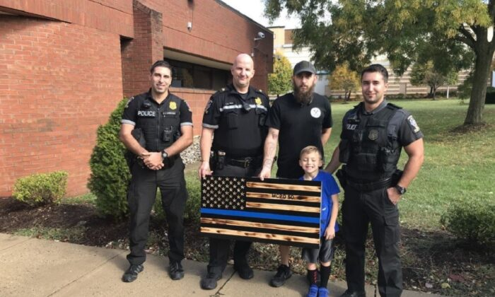 """James Shelton, center, with his son and police officers posing with the """"thin blue line"""" flag. (Montgomery County Police Department)"""
