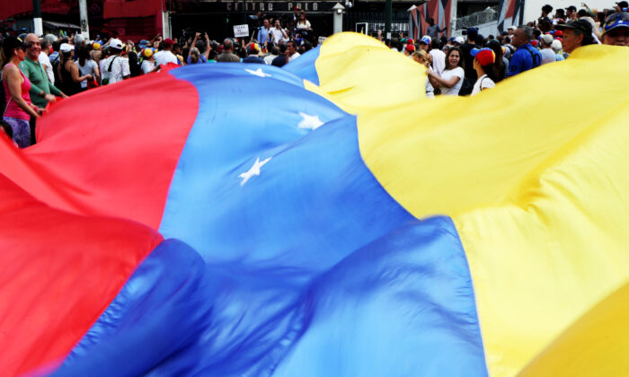 People display a huge Venezuelan flag as they take part in a protest against Venezuelan President Nicolas Maduro's government in Caracas, Venezuela, April 10, 2019. (Ivan Alvarado/Reuters)