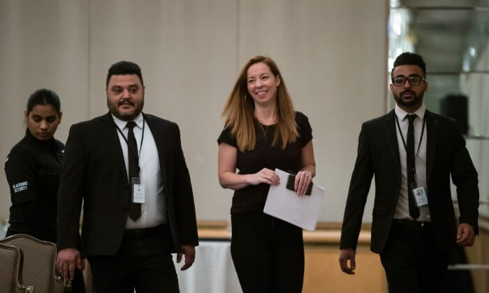 Writer Meghan Murphy is flanked by security before speaking at a panel discussion on gender identity in Vancouver on Nov. 2, 2019. (THE CANADIAN PRESS/Darryl Dyck)