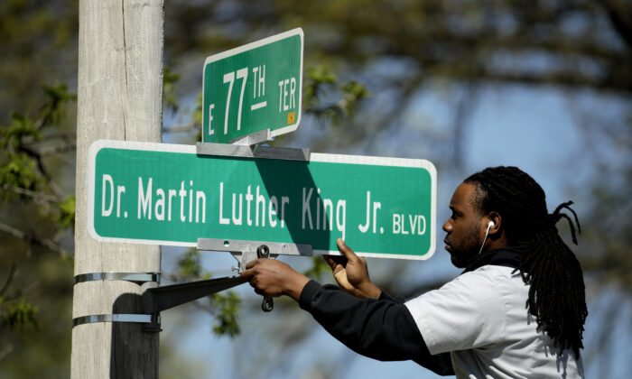In this April, 20, 2019, file photo, a public works employee changes a street sign from The Paseo to Dr. Martin Luther King Jr. Blvd. in Kansas City, Mo. AP Photo/Charlie Riedel, File