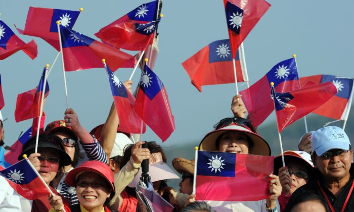Taiwanes golf fans wave their national flag during the trophy ceremony after the final round in the LPGA Thailand golf tournament at the Pattaya resort on February 20, 2011. (PORNCHAI KITTIWONGSAKUL/AFP via Getty Images)