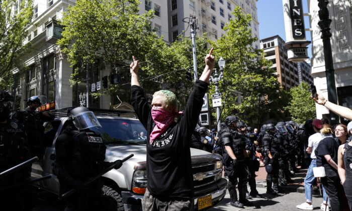 An unidentified Rose City Antifa member flicks off to the police during a demonstration between the left and right at Pioneer Courthouse Square on June 29, 2019 in Portland, Oregon. Moriah Ratner/Getty Images