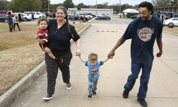 Recently released inmate Donnie Crow (L) holds her 17-month-old son Fayedon Davis as she walks from the Eddie Warrior Correctional Center with Christopher Davis Sr. and son 32-month old Christopher Davis II, following her release in Taft, Okla., on Nov. 4, 2019. (Sue Ogrocki/AP Photo)