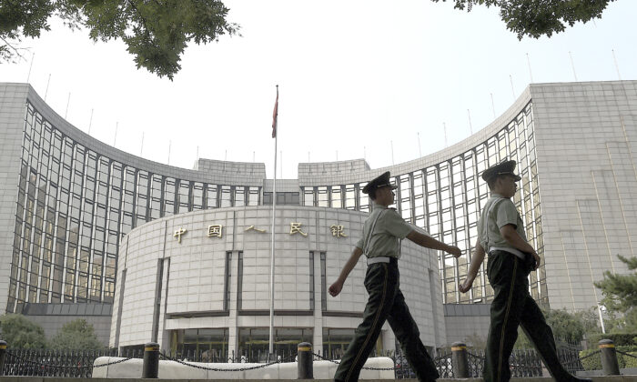 Paramilitary policemen patrol in front of the People's Bank of China, the central bank of China, in Beijing on July 8, 2015. (Greg Baker/AFP/Getty Images)