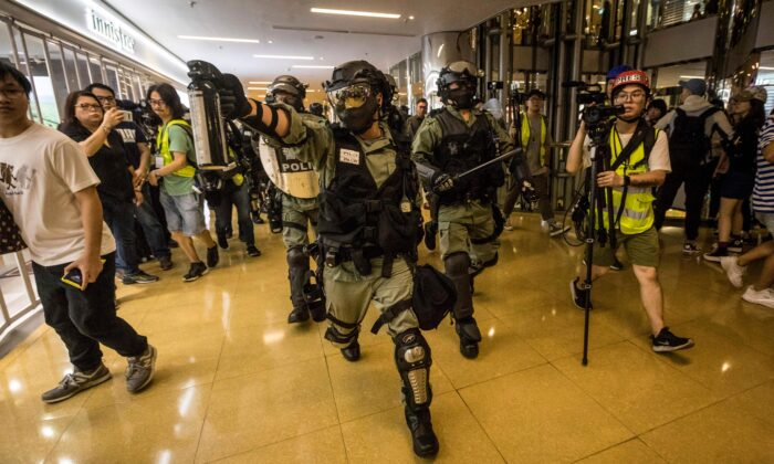 A riot police officer chases a protester while wielding a can of pepper spray inside the City Plaza mall in the Tai Koo Shing area in Hong Kong on Nov. 3, 2019.  (Vivek Prakash/AFP via Getty Images)