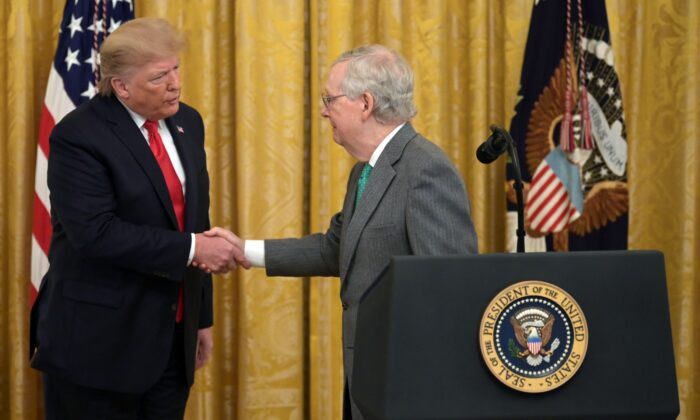 President Donald Trump and Senate Majority Leader Mitch McConnell (R) shake hands at the White House on Nov. 6, 2019. (Jim Watson/AFP via Getty Images)