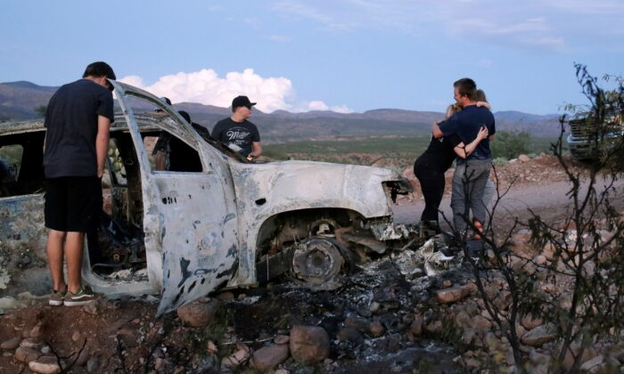 Relatives of slain members of Mexican-American families belonging to Mormon communities observe the burnt wreckage of a vehicle where some of their relatives died, in Bavispe, Sonora state, Mexico, on Nov. 5, 2019. (Jose Luis Gonzalez/Reuters)
