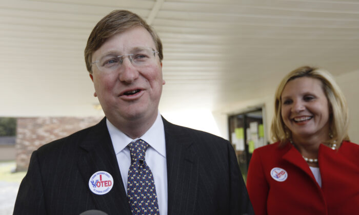Lt. Gov. Tate Reeves, left, speaks with reporters while his wife Elee Reeves, laughs at his response outside their Flowood, Miss., voting precinct, on Nov. 5, 2019. (AP Photo/Rogelio V. Solis)