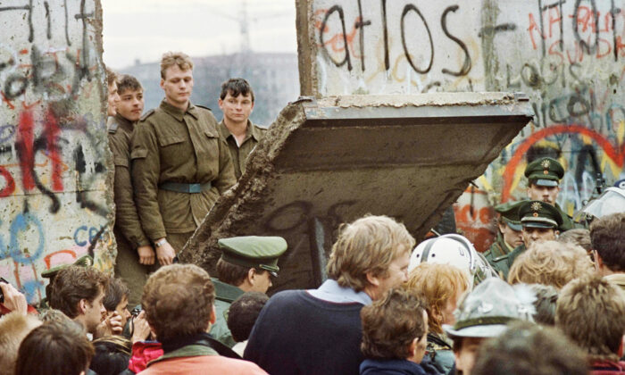 West Berliners crowd in front of the Berlin Wall early Nov. 11, 1989, as they watch East German border guards demolishing a section of the wall. (Gerard Malie/AFP via Getty Images)