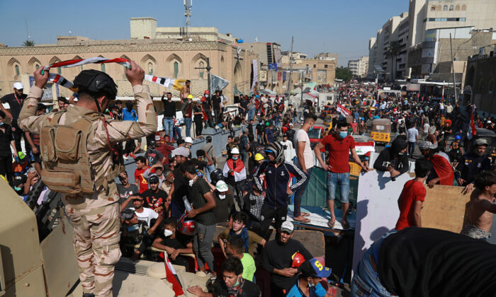 Iraqi Army soldiers trying to prevent protesters from crossing the al- Shuhada (Martyrs) bridge in central Baghdad, Iraq, Nov. 6, 2019. (AP Photo/Khalid Mohammed)