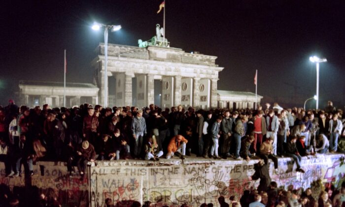 Thousands of young East Berliners crowd atop the Berlin Wall, near the Brandenburg Gate, in Germany, on Nov. 11, 1989. The wall came down on Nov. 9, 1989. (Gerard Malie/AFP/Getty Images)