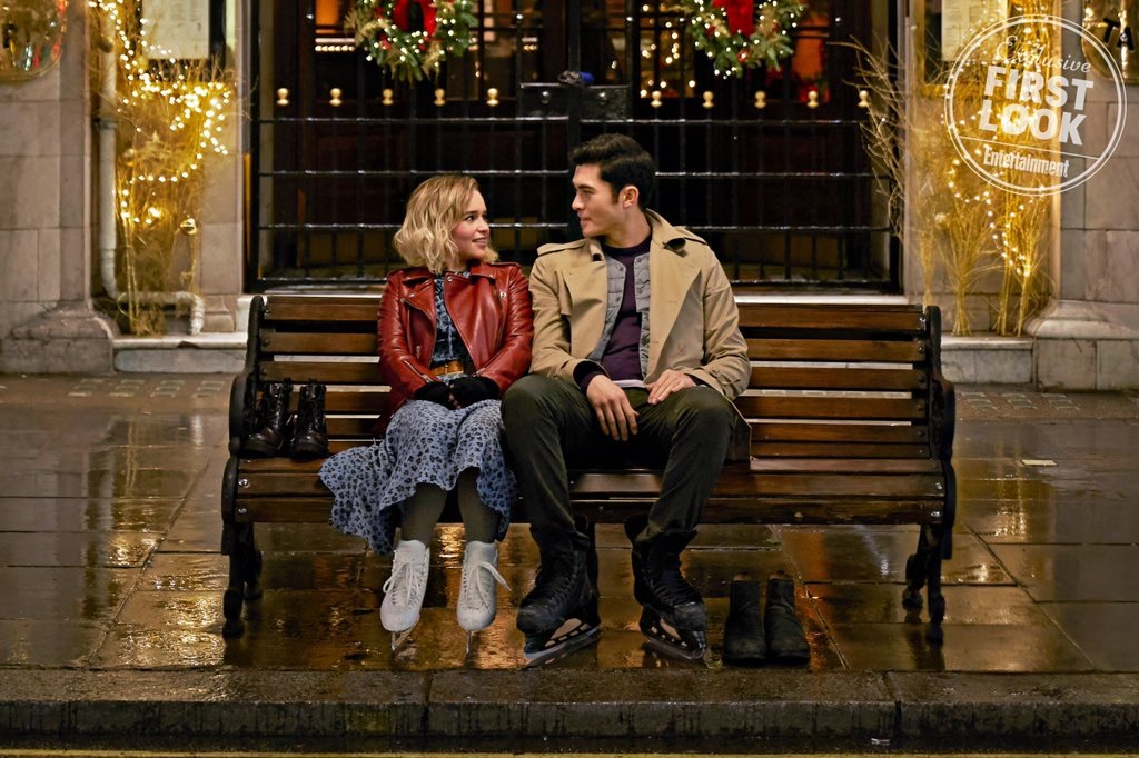 man and woman on park bench with ice skates