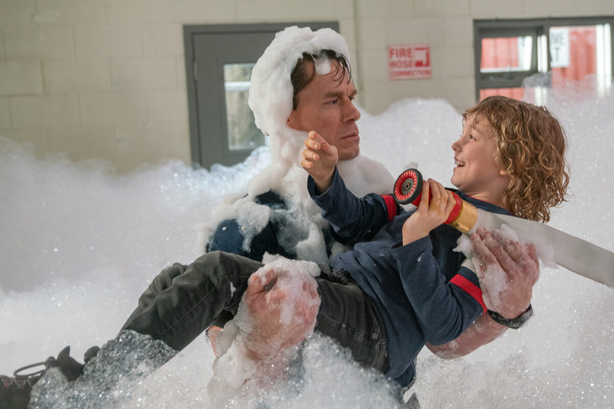 Fireman and boy in bubble-filled firehouse