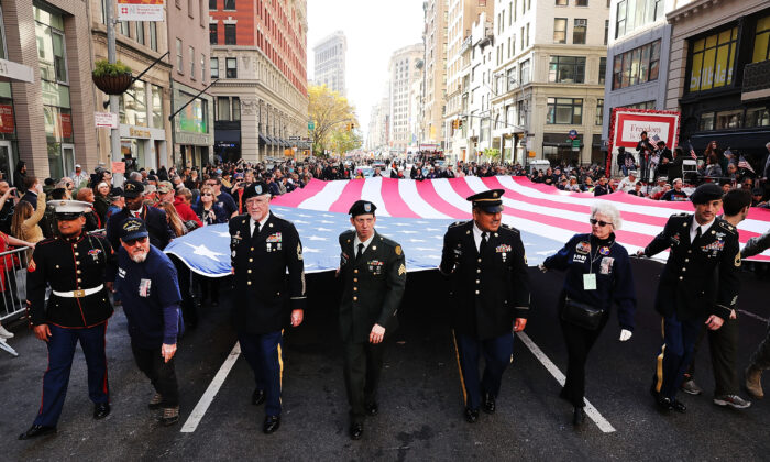 Veterans and others carry a large American Flag while marching in the nation's largest Veterans Day Parade in New York City on Nov. 11, 2016 in New York City. (Spencer Platt/Getty Images)