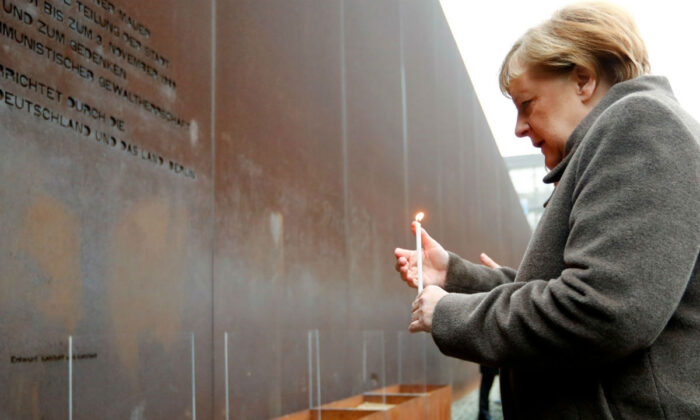 German Chancellor Angela Merkel lights a candle at the memorial of the divided city and the victims of communist tyranny during a ceremony marking the 30th anniversary of the fall of the Berlin Wall at the Wall memorial on Bernauer Strasse in Berlin, Germany on Nov. 9, 2019. (Fabrizio Bensch/Reuters)