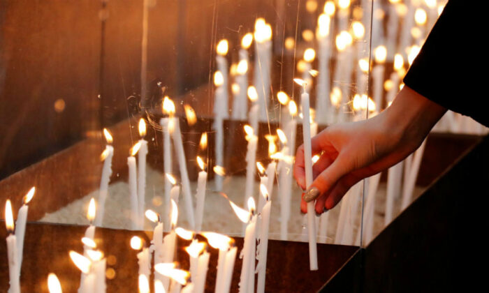 A person lights a candle at the memorial of the divided city and the victims of communist tyranny during a ceremony marking the 30th anniversary of the fall of the Berlin Wall at the Wall memorial on Bernauer Strasse in Berlin, Germany on Nov. 9, 2019. (Fabrizio Bensch/Reuters)