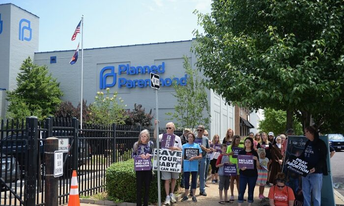 A group of demonstrators display signs during a pro-life rally outside the Planned Parenthood Reproductive Health Center in St Louis on on June 4, 2019. (Michael B. Thomas/Getty Images)