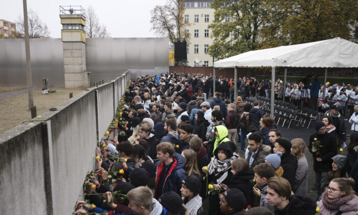 Young people stuck flowers in remains of the Berlin Wall during a commemoration ceremony to celebrate the 30th anniversary of the fall of the Berlin Wall at the Wall memorial site at Bernauer Strasse in Berlin,  Nov. 9, 2019. (Markus Schreiber/AP Photo)
