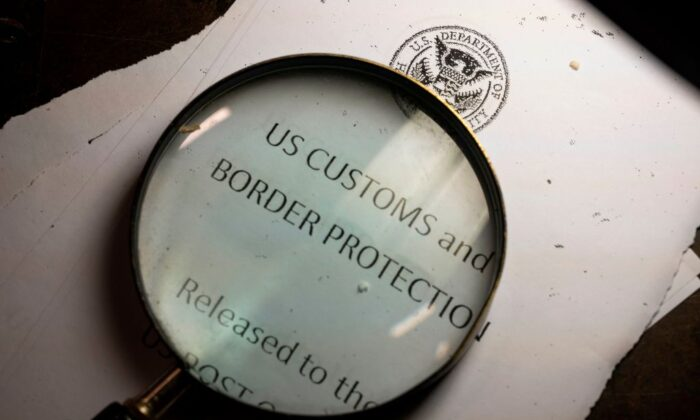 A magnifying glass is seen next to a logo of the Customs and Border Protection, Trade and Cargo Division at John F. Kennedy Airport's US Postal Service facility in New York on June 24, 2019. (Johannes Eisele /AFP via Getty Images)