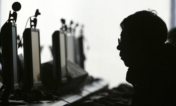 A computer user is silhouetted with a row of computer monitors at an Internet cafe. (AP Photo)