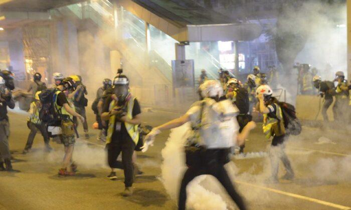 Police fire tear gas toward journalists in a shopping mall in Tsuen Wan, Hong Kong, on Nov. 10, 2019. (Gordon Yu/The Epoch Times)
