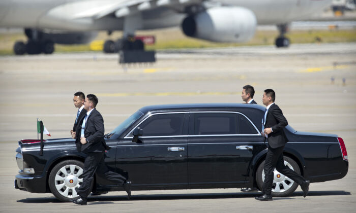 Chinese security personnel jog alongside a car carrying Italian Prime Minister Giuseppe Conte as he arrives at Beijing Capital International Airport to attend the Belt and Road Forum in Beijing on April 26, 2019. (MARK SCHIEFELBEIN/AFP via Getty Images)