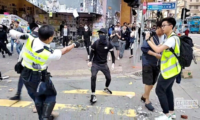 A still image from a social media video shows a police officer aiming his gun at a protester in Sai Wan Ho, Hong Kong, China, on Nov. 11, 2019. (Cupid Producer via Reuters)