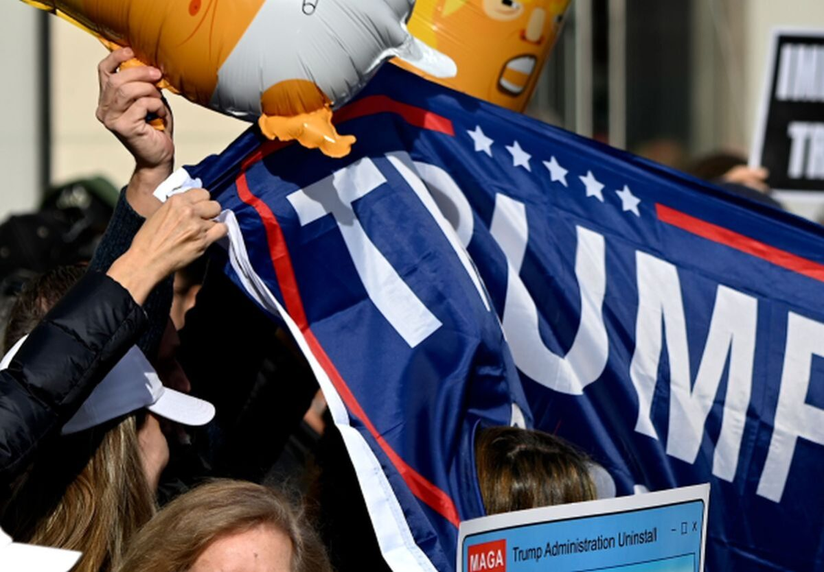 People hold signs during a rally against Trump