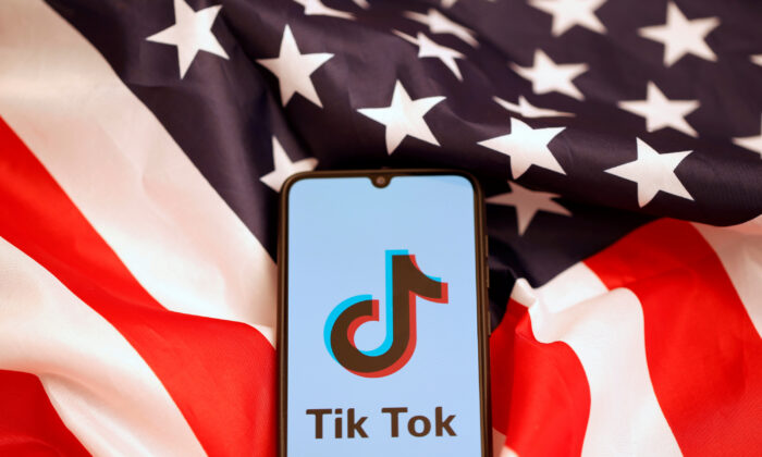 The TikTok logo is displayed on the smartphone while standing on the U.S. flag in this illustration picture taken on Nov. 8, 2019. (Dado Ruvic/Reuters)