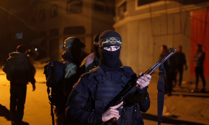 A Palestinian Islamic Jihad extremist stands guard at the scene of an Israeli strike that killed the group's field commander Baha Abu Al-Atta in Gaza City on Nov. 12, 2019. (Mohammed Salem/Reuters)