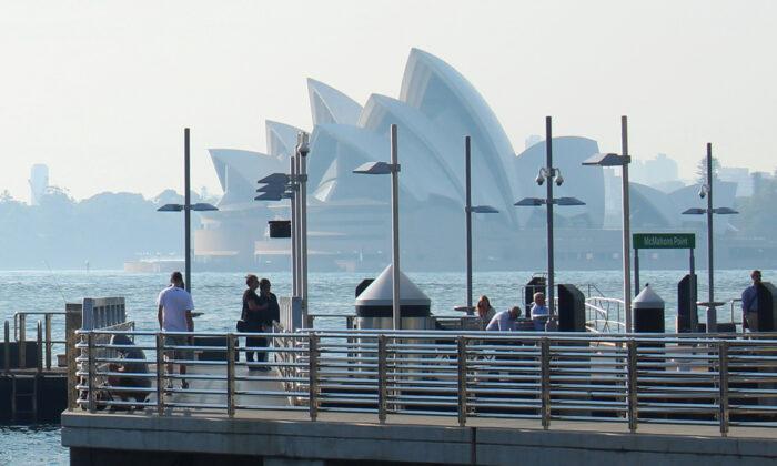 Commuters wait for a ferry as smoke from bushfires shrouds the Sydney Opera House in Sydney, Australia, on Nov. 12, 2019.  (Jonathan Barrett/Reuters)