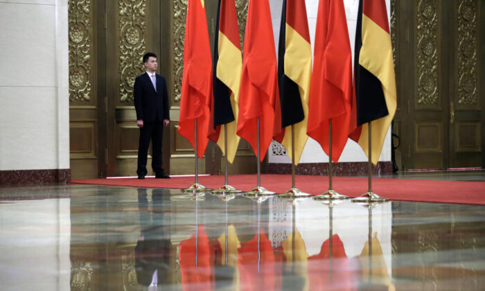 A security personnel stands guard next to Chinese and German flags during a meeting between China's President Xi Jinping and German Chancellor Angela Merkel at the Great Hall of the People in Beijing on May 24, 2018. (Jason Lee/AFP via Getty Images)
