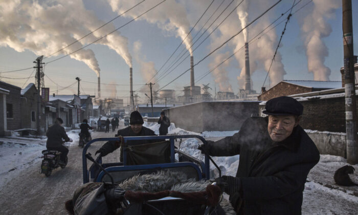 Smoke billows from stacks as Chinese men pull a tricycle in a neighborhood next to a coal fired power plant in Shanxi, China, on Nov. 26, 2015. (Kevin Frayer/Getty Images)