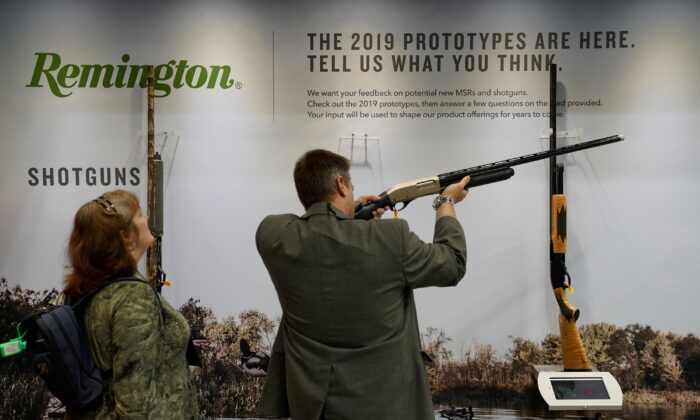 Attendees examine a Remington shotgun at the National Rifle Association's annual meeting, in Indianapolis, Indiana, on April 28, 2019. (Bryan Woolston/Reuters)