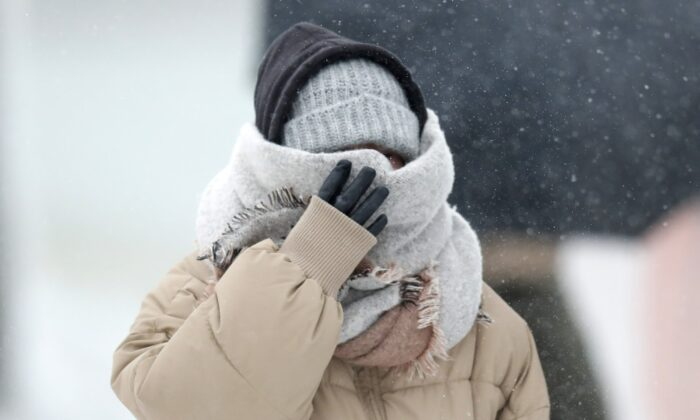 A woman walking the half mile from the Chicago Aquarium to the Adler Planetarium braces in a stiff wind and blowing snow off Lake Michigan on Nov. 11, 2019, in Chicago. (Charles Rex Arbogast/AP Photo)