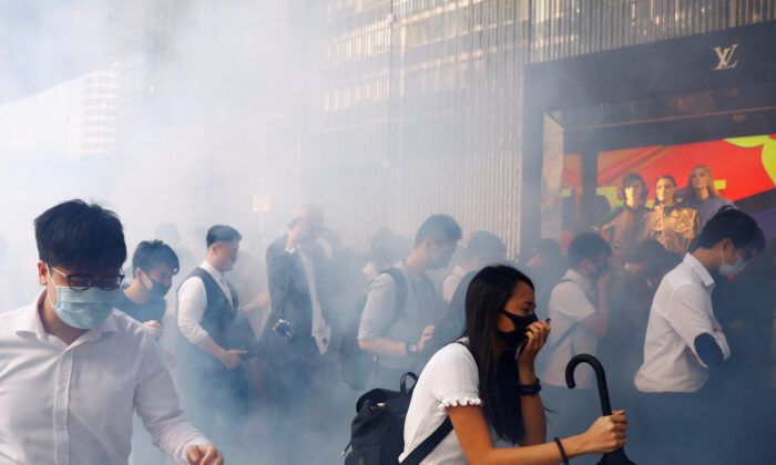 Office workers react after police fired tear gas, in Central, Hong Kong, China on Nov. 11, 2019. (Thomas Peter/Reuters)