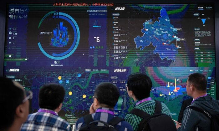 Visitors look at an AI (Artificial Inteligence) security software program on a screen at the 14th China International Exhibition on Public Safety and Security at the China International Exhibition Center in Beijing on Oct. 24, 2018. (NICOLAS ASFOURI/AFP via Getty Images)