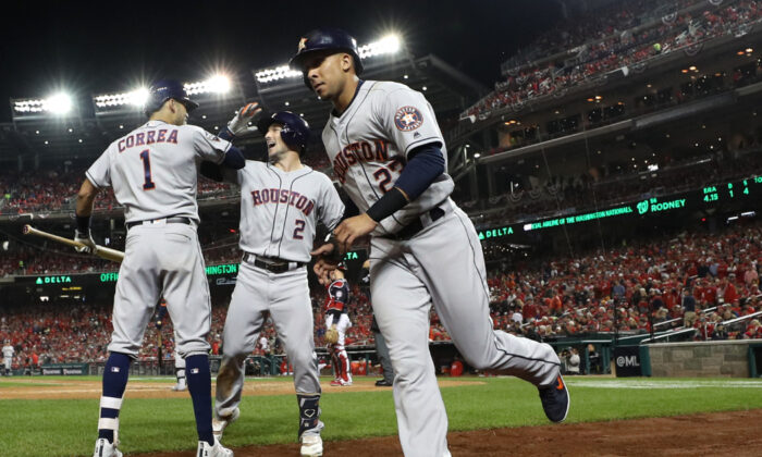 Houston Astros celebrate after hitting a grand slam home run against the Washington Nationals during the seventh inning in Game Four of the 2019 World Series at Nationals Park in Washington, DC on Oct. 26, 2019. (Patrick Smith/Getty Images)