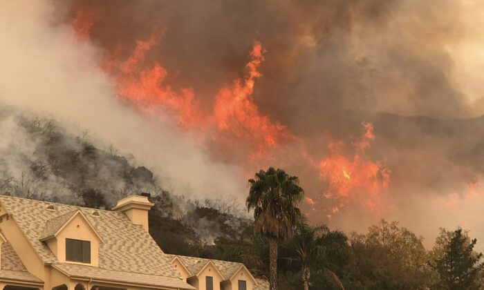 The Santa Barbara County Fire Department shows flames from a back firing operation underway rise behind a home off Ladera Ln near Bella Vista Drive in Santa Barbara, Calif., on Dec. 14, 2017. (Mike Eliason/Santa Barbara County Fire Department via AP Photo)