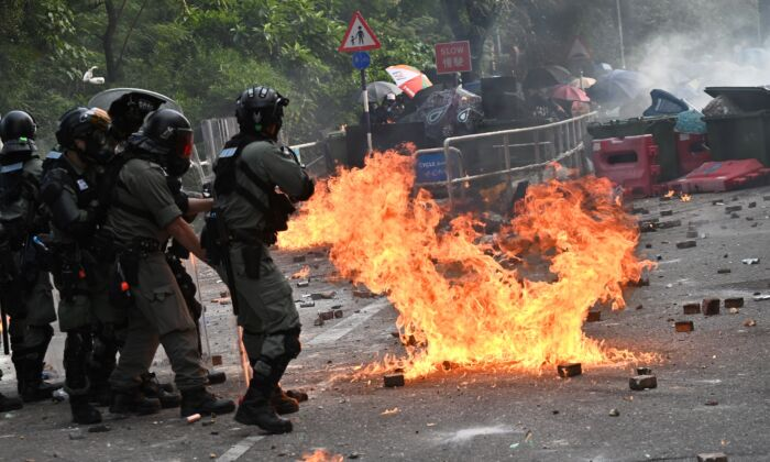 Police fire tear gas toward protesters at the Chinese University of Hong Kong, in Hong Kong on Nov. 12, 2019. Protesters struck the city's transport network for a second day running after police shot a young demonstrator and another man was set on fire. (PHILIP FONG/AFP via Getty Images)