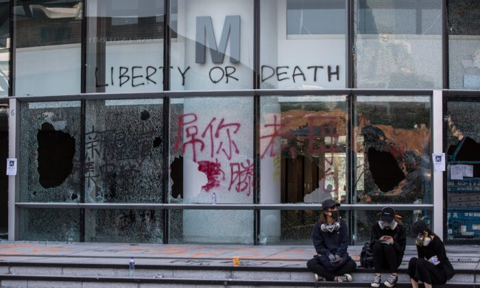 Protesters sit on the steps in front of a damaged building inside The Hong Kong Polytechnic University on Nov. 14, 2019. (Isaac Lawrence/AFP via Getty Images)