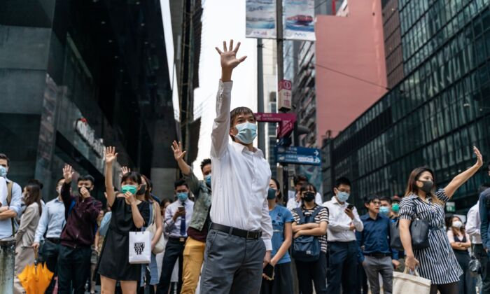 Pro-democracy supporters make gestures as they occupy a street in Central district in Hong Kong on November 14, 2019. (Anthony Kwan/Getty Images)
