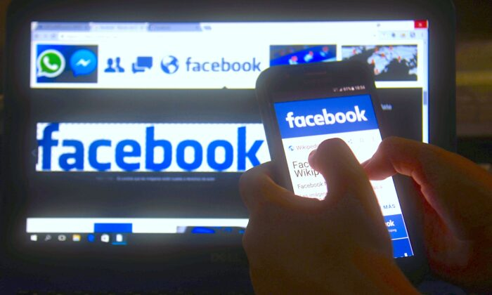 A cellphone and a computer screen display the logo of the social networking site Facebook on March 22, 2018. (Norberto Duarte/AFP via Getty Images)